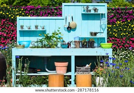 Outdoor kitchen, Kitchenware on blue wooden wall, kitchen in the flowers garden.