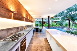 Outdoor kitchen with a stove an countertop next to garden including a pool in luxury hotel or house