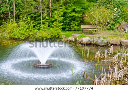 Outdoor landscape garden with pond and fountain in North Vancouver, British Columbia, Canada. Sunset light.