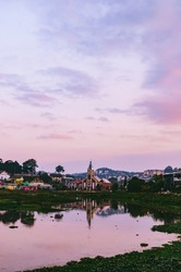 Outdoor landscape photo of a small church with a broken bell tower on the bank of a small lake. Reflection of the colorful twilight sky and the church building create a beautiful scene. Dalat, Vietnam