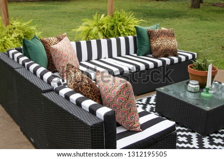 Outdoor lawn furniture with black and white crisply striped upholstery and assorted pillows grouped around a table with ferns on a patio in yard with grass and trees
