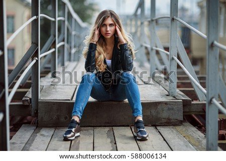 Photo of Outdoor lifestyle fashion portrait of pretty young girl, wearing in hipster swag grunge style on urban background. Retro vintage toned image, film simulation