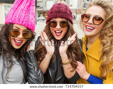 Outdoor lifestyle fashion portrait of three pretty cheerful girls friends, smiling and having  fun.  Walking on the city. Wearing stylish bright outerwear, hats and sunglasses. Positive emotions - Shutterstock ID 714704557