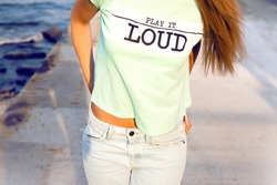 Outdoor lifestyle hipster teen girl posing alone,wear cool designer t-shirt,with music icon.Warm vintage bright colors.toned,T -shirts with prints,bright T-shirt with the words,Printed,youth jersey