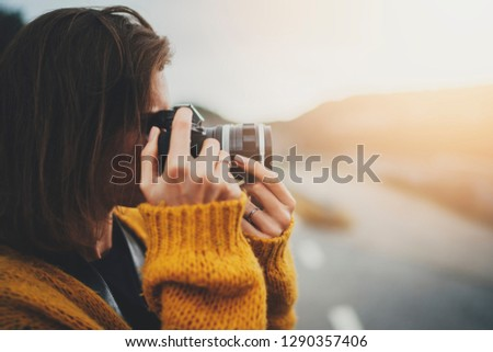 Outdoor lifestyle image of pretty young woman having fun traveling in Europe with vintage camera, Travel photo of attractive girl making pictures on film camera in hipster trendy look