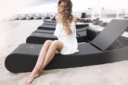 Outdoor lifestyle portrait of amazing glamorous luxury woman posing on vacation,beach Elegant classic clothes in white and pastel colors.Sensual smile,stunning face.Soft colors.white dress,curly hair