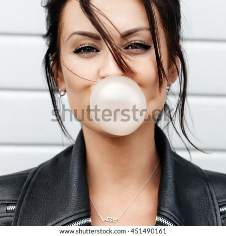 Stock Photo Outdoor lifestyle portrait of beautiful young woman blowing a bubble gum balloon