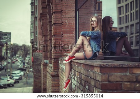 Photo of Outdoor lifestyle portrait of pretty young sitting girl, wearing in hipster swag grunge style urban background. Retro vintage toned image, film simulation.
