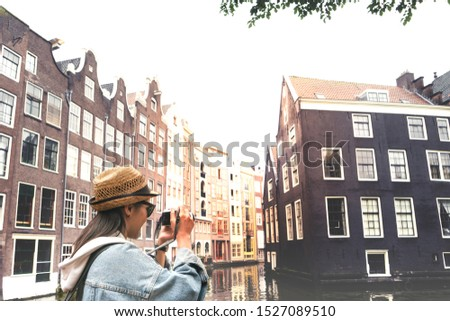 Outdoor lifestyle portrait of pretty young woman having fun in the city in Europe with digital camera travel photo of photographer Making pictures in hipster style