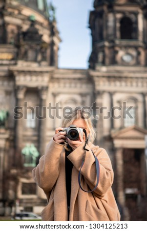 Outdoor lifestyle portrait of pretty young woman on old building background. Girl having fun in the city in Europe with camera. Travel photo of photographer. Making pictures