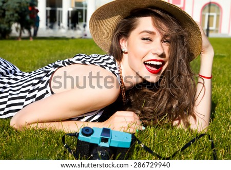 Stock Photo Outdoor lifestyle portrait of stylish girl laughing and smiling holding retro camera.Beautiful sexy woman,evening makeup wearing short dress,summer fall collection perfect in park sun shine,top skirt
