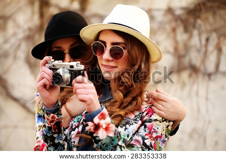 Outdoor lifestyle portrait of two best friends hipsters making photo on their vintage camera having fun together joy and happiness wearing trendy bright clothes and sunglasses