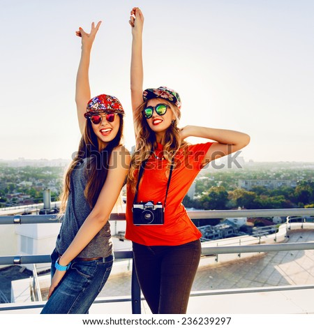 Outdoor lifestyle portrait of two crazy happy best friend girls screaming and put their hands to the air, enjoy amazing view from the roof at sunset, wearing trendy bright clothes caps and sunglasses.