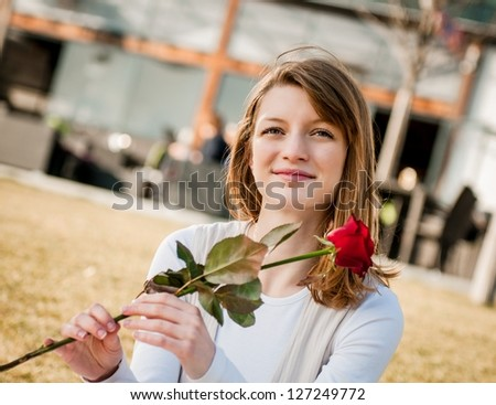 Outdoor lifestyle portrait of young woman daydreaming  with red rose