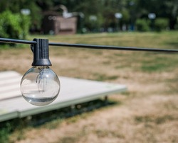 Outdoor light bulb hanging from a wire.