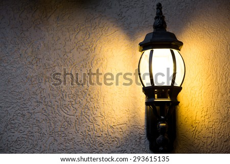 Outdoor light fixture on in the dark on a textured background
