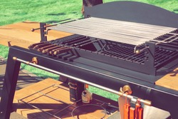 Outdoor luxury Combo Grill Table. Backyard Kitchen Table With BBQ Charcoal Grill Appliance. Family Garden Party Barbecue Grill, Closeup View, Green Backyard Lawn In The Background.