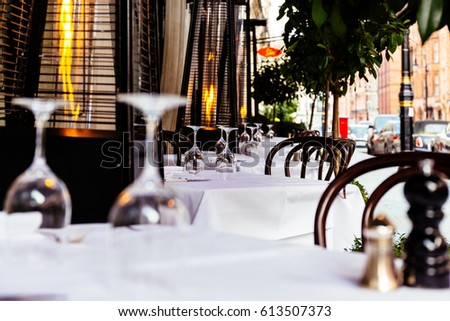 Outdoor luxury restaurant terrace tables and chairs in mayfair London with gas heater pyramid