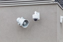 Outdoor megaphone security camera on the wall of building. Loudspeakers and cctv tracking security camera.