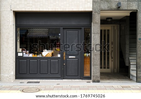 Outdoor mock up of store and shop front template - front view vintage black grey shop tone  with windows display, and tea making, doll decoration. Foto d'archivio ©