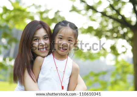 Outdoor park happy Asian mother and daughter