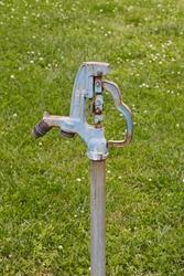 outdoor park water faucet in green grass.