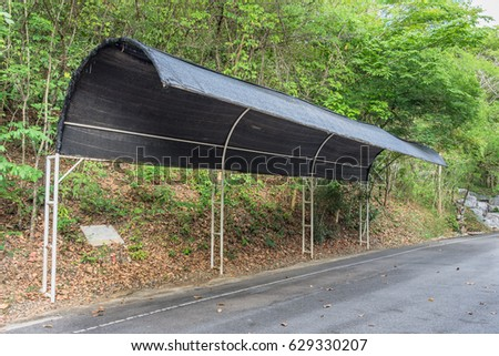 Outdoor parking roof in park made with black shading net  #629330207