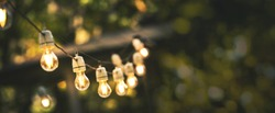 outdoor party string lights hanging in backyard on green bokeh background with copy space