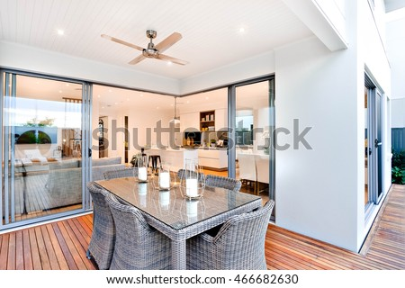 Outdoor patio area with table set up beside an entrance to inside of a modern house with a kitchen, there are candles on the table under the fan