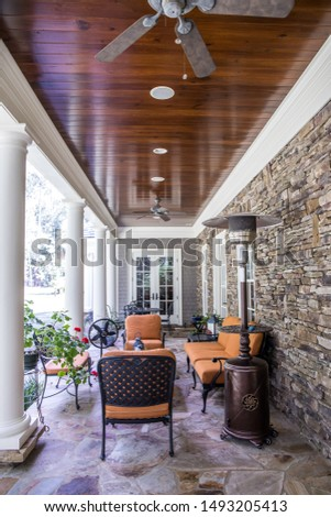 outdoor patio porch of traditional upgraded custom home with seating for entertaining and dining and a dark wood stained ceiling #1493205413