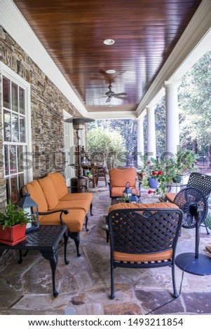 outdoor patio porch of traditional upgraded custom home with seating for entertaining and dining with rust orange colors