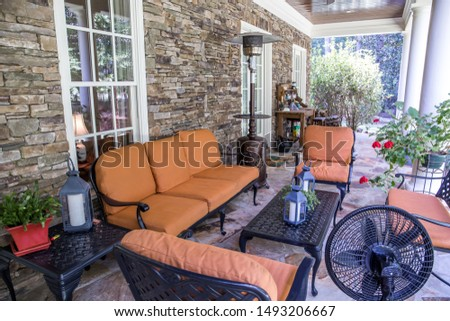 outdoor patio porch of traditional upgraded custom home with seating for entertaining and dining in orange and rust colors