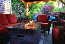 Outdoor patio set with a gas fireplace a glass of scotch whiskey on ice and potted flowers under a gazebo