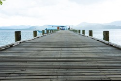 Outdoor perspective shot of wooden bridge walkway down to ship dock or pier in the ocean. With beautiful tropical nature, sky, cloud and sea waves at the background.