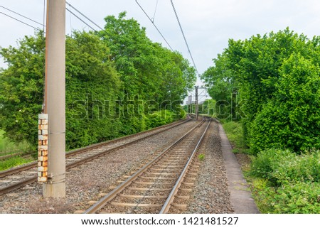 Outdoor perspective view of railway track lines without train from platform  train station surrounded with green fresh bush, shrub and trees in countryside area in Germany  against cloudy sky. #1421481527