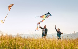 Outdoor photo of a father with daughter as they releasing colorful kites on the high grass meadow sincerely laughing. Warm family moments or outdoor time spending concept image.