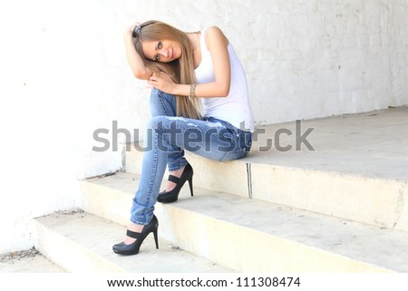 Outdoor photo of pretty girl sitting on the floor in grungy setting.