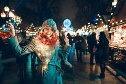Outdoor photo of young beautiful happy smiling girl holding sparklers, posing in street. Festive Christmas fair on background. Model wearing stylish winter coat, knitted beanie hat, scarf.