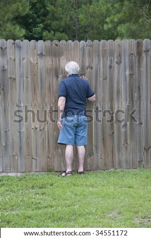 Outdoor photograph of an adult man peeking through a hole in the fence.  He is a nosy neighbor!