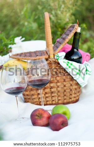 Outdoor picnic setting with red wine and fruits