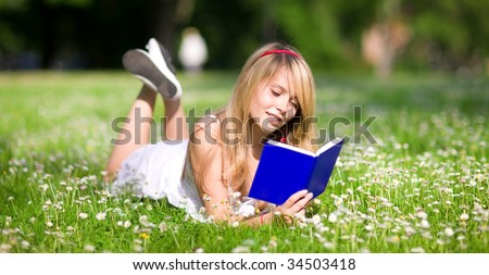 outdoor picture of lovely teenage girl with book