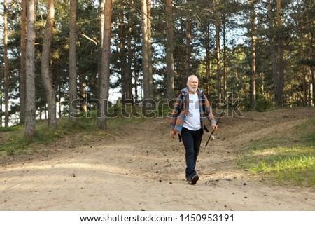 Outdoor picture of sad elderly bearded man with fishing rod going along path in woods, having disappointed facial expression because he caught no fish at all. on fishing spot Activity and recreation