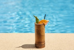 Outdoor picture of wooden cup with cocktail being near swimming pool, green and piece of orange being inside cocktail, black straw to drink, getting rid of thirst, cold drink in hot weather.