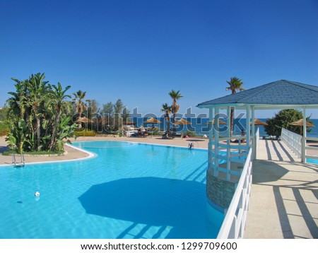 Outdoor pool in hotel and resort with palm tree and chairs around. Vieste, Italy - August 2015 #1299709600