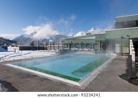 outdoor pool which is steaming  at a cold and clear winter day and mountains in the background