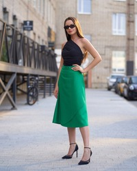 Outdoor portait of young beautiful eleganr woman wearing black top and green skirt and posing at city street