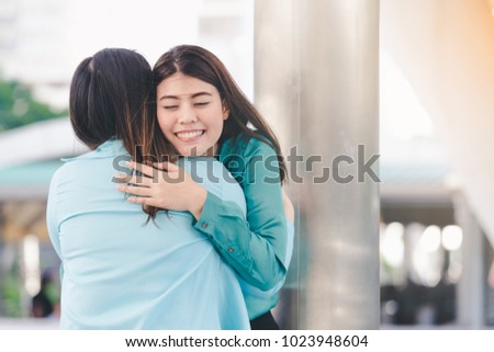Outdoor Portrait happy Asian woman and friend hugging each other comforting each other on a weak day to become strong again city background