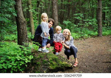 Outdoor portrait of a amazing family walking together in forest park