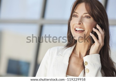 Outdoor portrait of a beautiful happy brunette woman or businesswoman in her thirties talking on her cell phone