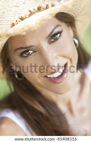 Outdoor portrait of a beautiful young brunette woman in her thirties wearing straw cowboy hat